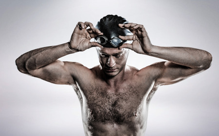 swimming goggles: Composite image of swimmer holding swimming goggles against grey background Stock Photo