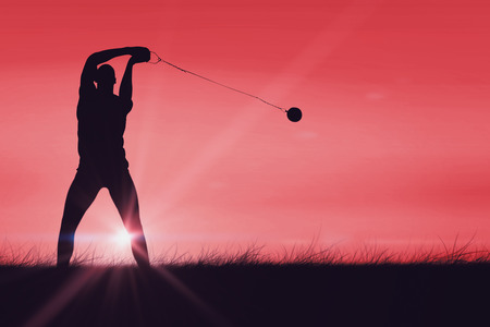 red sky: Front view of sportsman practising hammer throw against red sky over grass Stock Photo