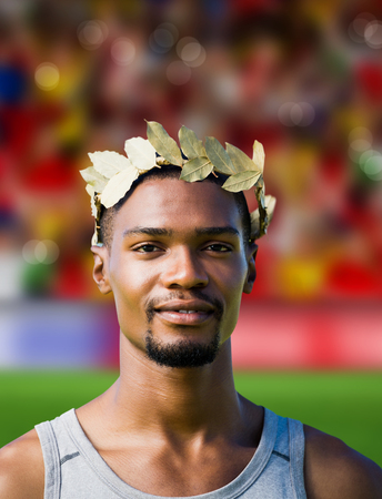 the victorious: Portrait of victorious sportsman with crown of laurels  against blurry football pitch with crowd