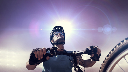 adventuring: Composite image of man cycling with mountain bike against sunlight Stock Photo