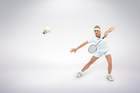 racket: Composite image of badminton player playing badminton against white background Stock Photo