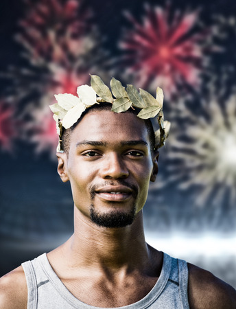 the victorious: Portrait of victorious sportsman with crown of laurels  against fireworks exploding over football stadium