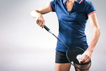 Composite image of badminton player holding a racket ready to serve against white background Stock Photo
