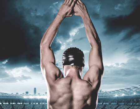 sky dive: Swimmer preparing to dive against composite image of stadium with cloudy sky