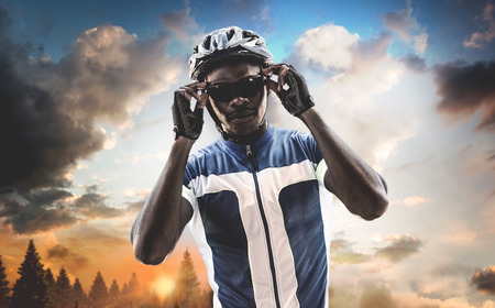 composite image: Composite image of cyclist is posing against landscape Stock Photo