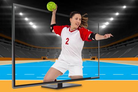 terrain de handball: Sportswoman lancer une balle contre terrain intérieur de handball Banque d'images