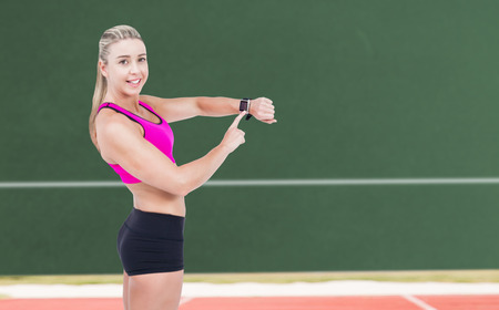 playing field: Female athlete using her smart watch against digitally generated image of playing field