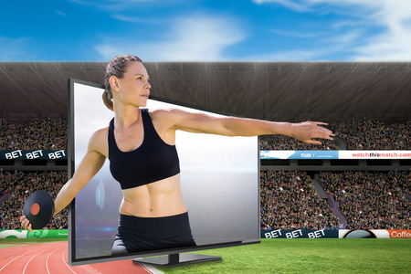 lanzamiento de disco: Concentrado deportista practicando el lanzamiento de disco contra el campo de fútbol americano