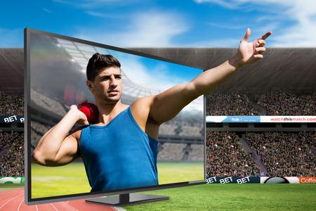 lanzamiento de bala: Front view of sportsman practising shot put  against view of a stadium Foto de archivo