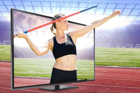 lanzamiento de jabalina: Vista frontal de la deportista practicando lanzamiento de jabalina contra la pista de carreras