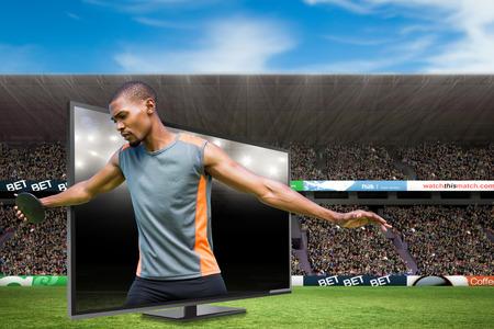 lanzamiento de disco: Vista frontal del deportista practicando el lanzamiento de disco contra el campo de fútbol americano