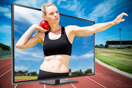 lanzamiento de bala: Vista frontal de la deportista practicando lanzamiento de peso en contra de vista de pista de atletismo