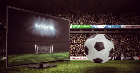 football pitch: Black and white leather football against football pitch and goal under spotlights