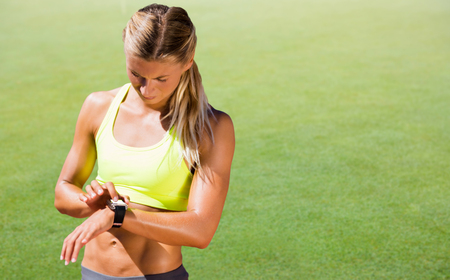 grassy: Sporty woman looking her watch against grassy landscape