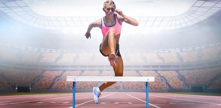 Atlética mujer que practica salto de obstáculos contra el punto de vista de un estadio