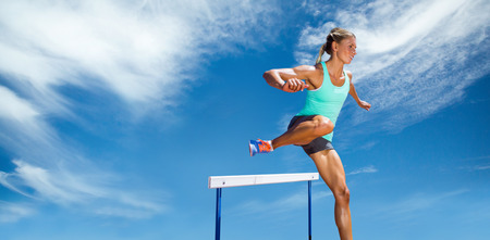 hurdles: Sportswoman practising the hurdles against view of a blue sky Stock Photo