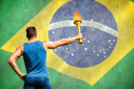legging: Rear view of athletic man holding a torch against digitally generated brazilian national flag Stock Photo