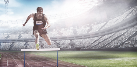 hurdles: Sportsman practising hurdles against view of a stadium Stock Photo