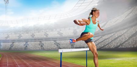 hurdles: Sportswoman practising the hurdles against view of a stadium