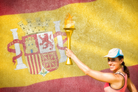 raise the white flag: Happy woman raising a cup  against digitally generated spanish national flag