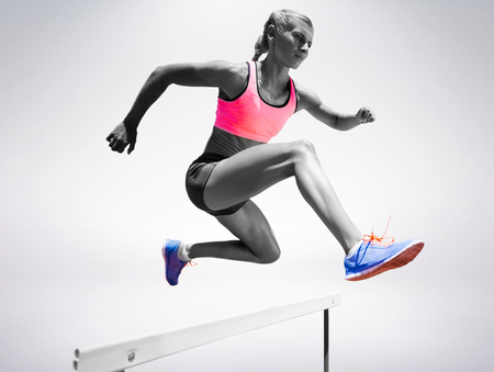 hurdle: Sporty woman jumping a hurdle against grey background Stock Photo