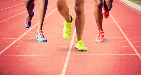 athletics track: Close up of sportsman legs running against focus of athletics track Stock Photo