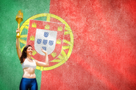 raise the white flag: Front view of sportswoman raising a cup against digitally generated portugese national flag