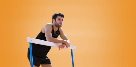hurdle: Athletic man pressed on a hurdle posing against orange background