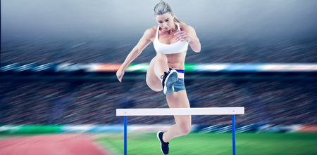 Female athlete jumping against view of a stadium Stock Photo