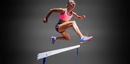 femme Sporty sauter un obstacle sur le fond noir
