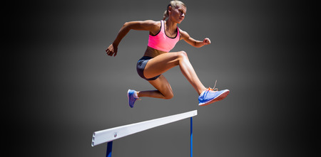 hurdle: Sporty woman jumping a hurdle against black background