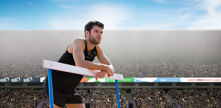 hurdle: Athletic man pressed on a hurdle posing against view of a stadium