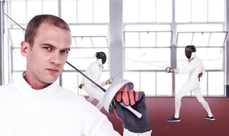 fencing sword: Close-up of swordsman holding fencing sword against gym Stock Photo