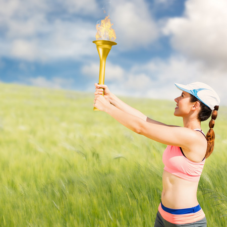 Sporty woman holding  torch against nature scene