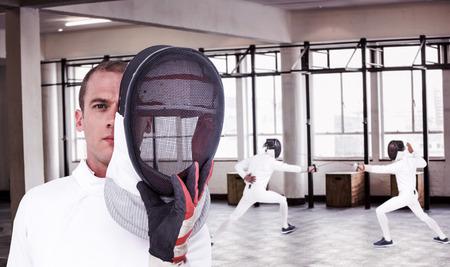 swordsman: Swordsman holding fencing mask against interior view of a gym