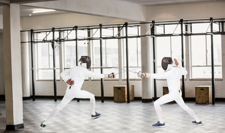 fencing sword: Man wearing fencing suit practicing with sword against interior view of a gym Stock Photo