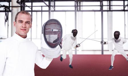 swordsman: Swordsman holding fencing mask against view of a gym