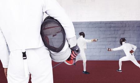 swordsman: Rear view of swordsman holding fencing mask and sword against gym