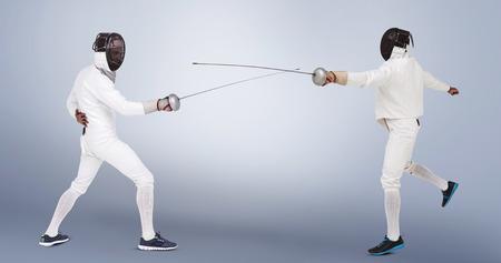 fencing sword: Man wearing fencing suit practicing with sword against grey vignette