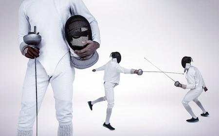 fencing sword: Swordsman holding fencing mask and sword against grey vignette