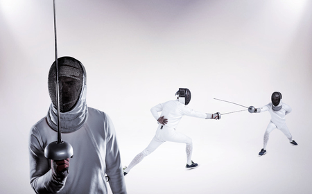 fencing sword: Man wearing fencing suit practicing with sword against grey background