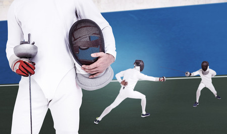 bi: Swordsman holding fencing mask and sword against digitally generated image of bi colored background Stock Photo