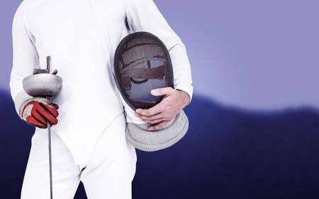 swordsman: Swordsman holding fencing mask and sword against blurred mountains Stock Photo