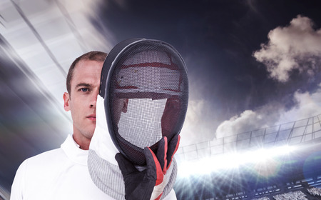 swordsman: Swordsman holding fencing mask against football stadium with fans in white