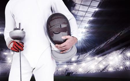 swordsman: Swordsman holding fencing mask and sword against sports arena Stock Photo