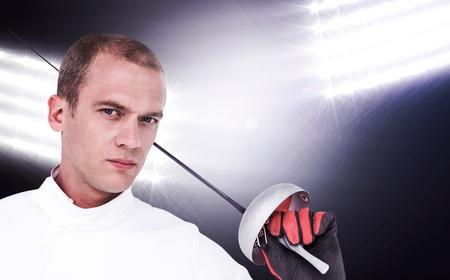 fencing sword: Close-up of swordsman holding fencing sword against spotlights