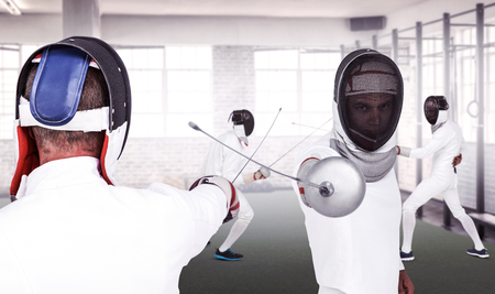 fencing sword: Man wearing fencing suit practicing with sword against gym
