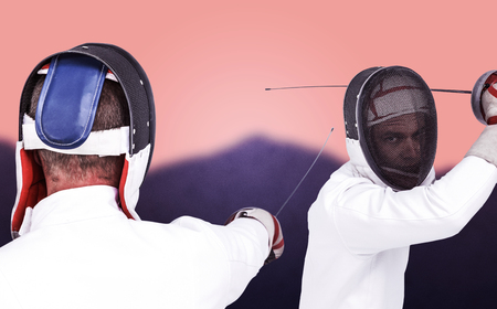 fencing sword: Man wearing fencing suit practicing with sword against blurred mountains