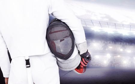 swordsman: Rear view of swordsman holding fencing mask and sword against sports arena