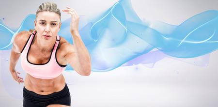 start line: Female athlete on the start line against blue wave Stock Photo